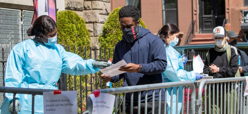 Medical personnel help residents sign in for a COVID-19 test at the Bethany Baptist Church on Wednesday in the Bedford-Stuyvesant neighborhood of the Brooklyn borough of New York.