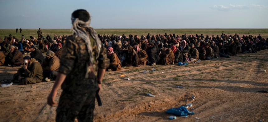 U.S.-backed Syrian Democratic Forces (SDF) fighters stand guard next to men waiting to be screened after being evacuated out of the last territory held by Islamic State group militants, near Baghouz, eastern Syria in February.