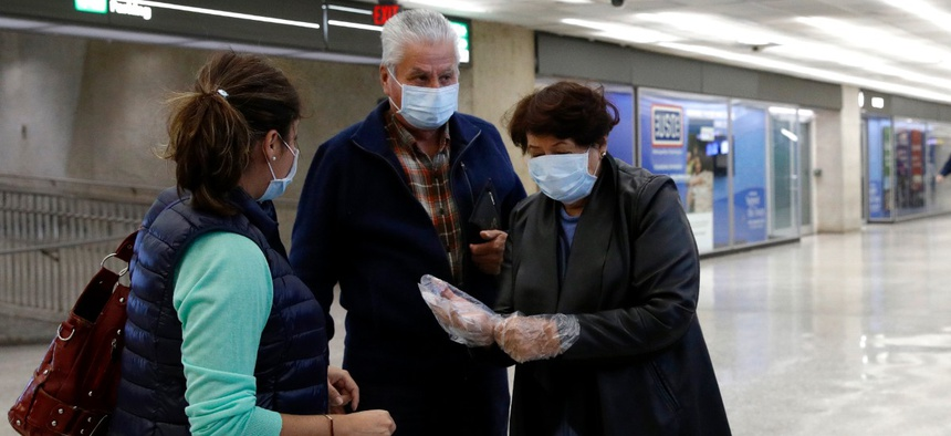 A woman wearing a face mask puts on plastic gloves in an arrivals area at Dulles International Airport in Dulles, Va., on March 17.