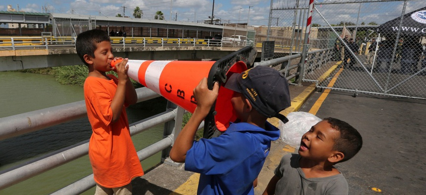 Migrant children play with Customs Border Protection traffic cone, after camping out on the Gateway International Bridge in October.