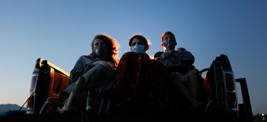 Moviegoers wear masks while watching a movie from a truck bed at Mission Tiki drive-in theater in Montclair, Calif., on May 28, 2020.
