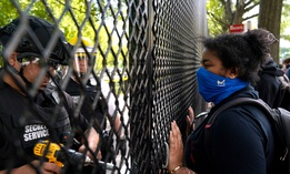 A demonstrator watches as a U.S. Secret Service police office works on a fence blocking Lafayette Park as protests in the death of George Floyd continue on Tuesday, June 2, near the White House.