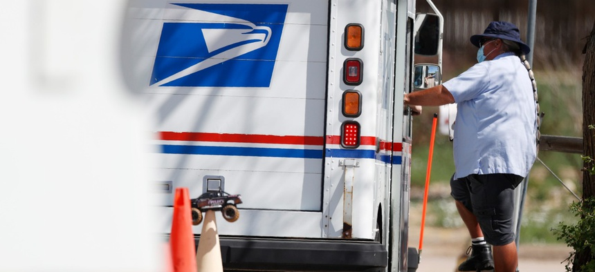 An instructor wears a face mask while directing a new hire on how to drive a delivery van at the U.S. Postal Service distribution facility, Friday, May 22, 2020, in east Denver.