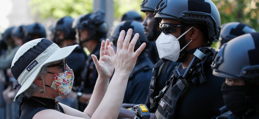 Rev. Susan Wilder of Kirkwood Presbyterian Church in Springfield, Va., prays at the police line, with a Bureau of Prisons Special Operations Response Team member, as demonstrators gather to protest the death of George Floyd on June 3 near the White House.
