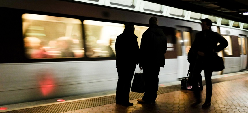 Agencies have mostly resisted bringing employees back to headquarters offices in Washington where coronavirus cases have been high. Above, commuters wait to board a metro train.