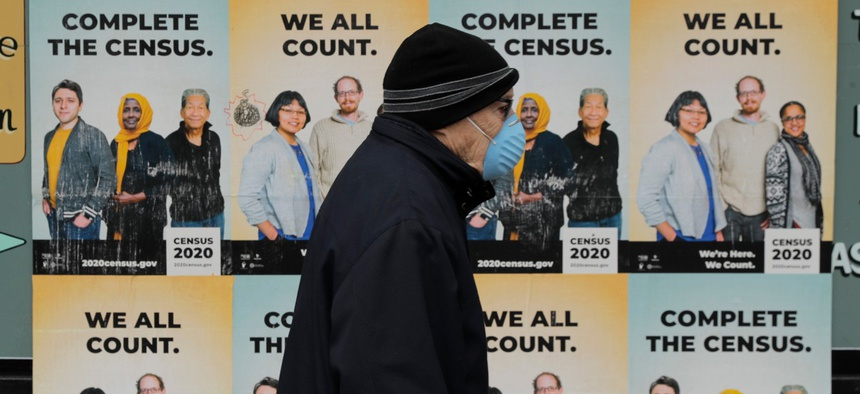 A man walks past posters encouraging participation in the 2020 census on April 1 in Seattle.