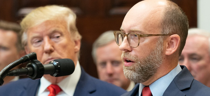 Acting White House Budget Director Russell Vought speaks at a news conference last fall as President Trump looks on.