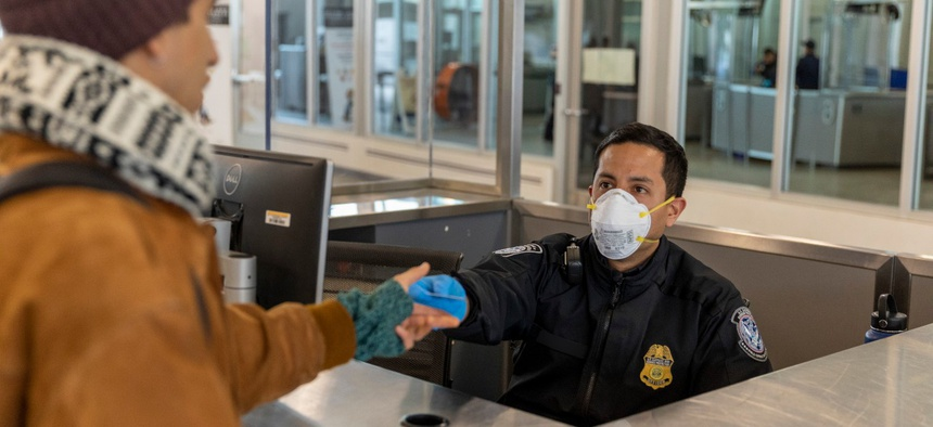 CBP officers at the San Ysidro Port of Entry, PED WEST facility, use personal protective equipment and social distancing to limit the spread of coronavirus.