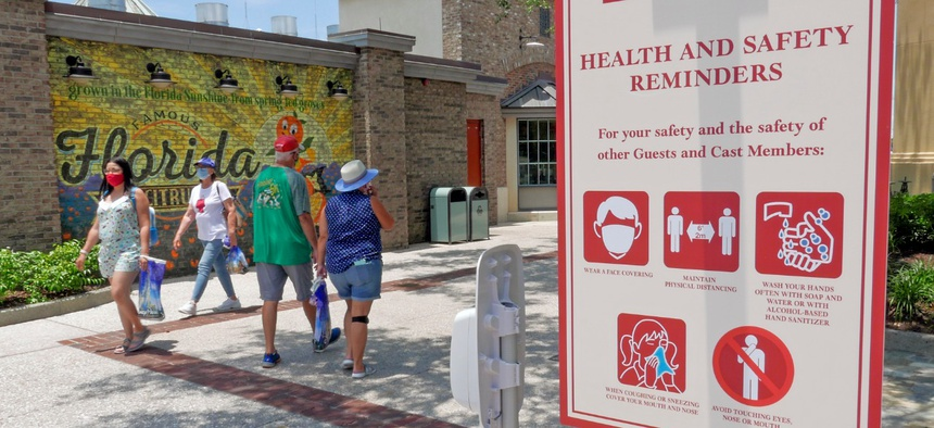 Signs remind patrons to wear masks and other protocols because of the coronavirus pandemic as they stroll through the Disney Springs shopping, dining and entertainment complex on June 16.