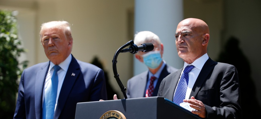President Donald Trump, left, listens as Moncef Slaoui, a former GlaxoSmithKline executive, speaks about the coronavirus vaccine effort in the Rose Garden of the White House on May 15.