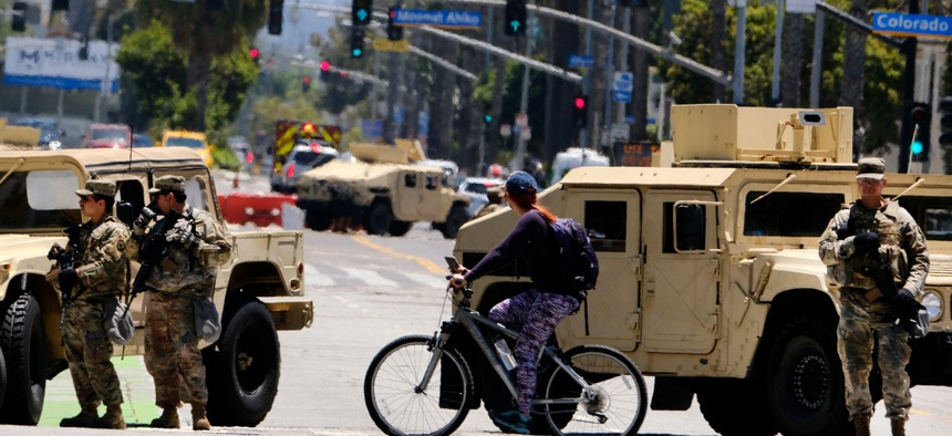 A cyclist rides past a road block with National Guard troops along Ocean boulevard in Santa Monica, Calif. on Sunday June 7.