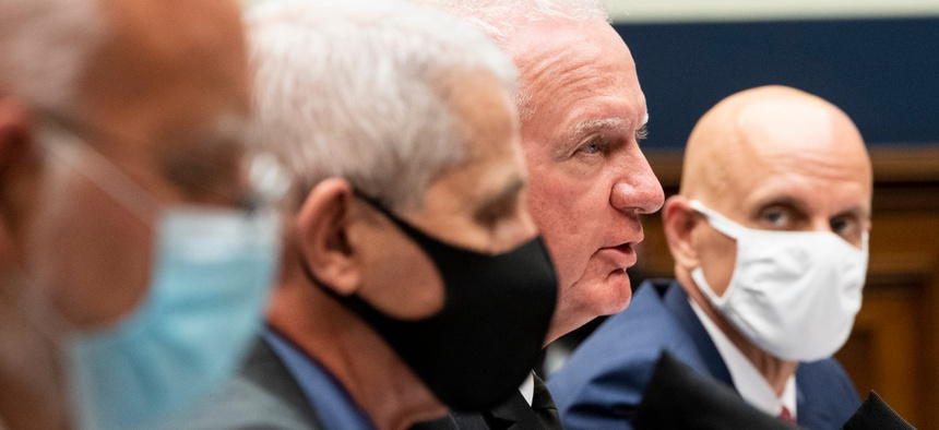 U.S. Public Health Service's Adm. Brett P. Giroir (unmasked) testifies alongside CDC Director Dr. Robert Redfield, left, NIAID Director Dr. Anthony Fauci and FDA Commissioner Dr. Stephen M. Hahn, right, during a hearing Tuesday.
