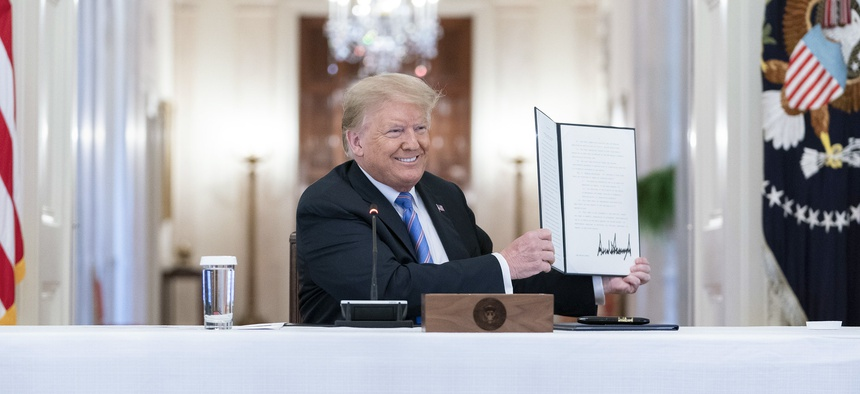 President Donald Trump displays his signature after signing the executive order on Friday.