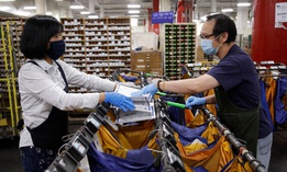 Postal workers sort mail at a USPS processing and distribution center in Oakland, California in April.