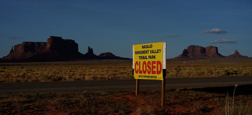A sign posted in Oljato-Monument Valley, Utah, says the Navajo Monument Vally Tribal Park is closed, in an effort to prevent the spread of COVID-19 on the Navajo reservation.