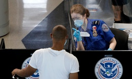 A Transportation Security Administration officer, right, talks with a passenger at a security checkpoint in O'Hare International Airport on June 16.