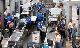 Transportation Security Administration agents process passengers at the south security checkpoint in Denver International Airport on June 10.
