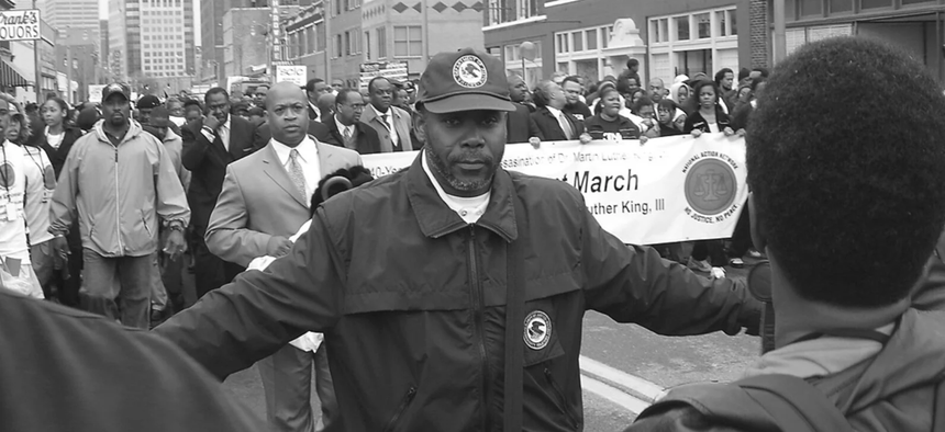 A staff member of the Community Relations Service mediating at a march in Memphis in 2009. His jacket and hat displayed the Department of Justice seal.