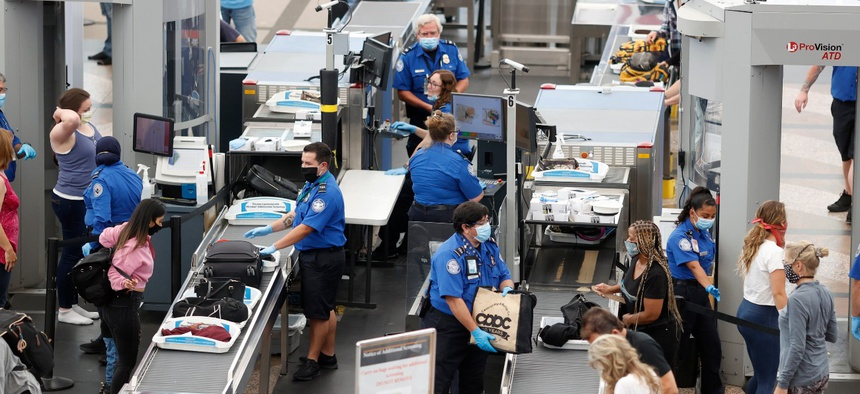 TSA agents work at the south security checkpoint in Denver International Airport in June. TSA has reported a total of 1,171 employees testing positive for COVID-19.