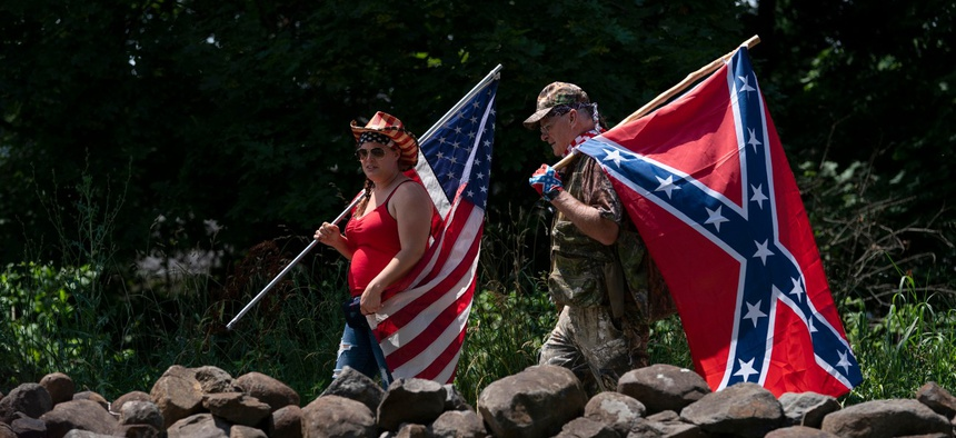 Tourists carry an American flag and a Confederate flag as they walk on a pathway at the Gettysburg National Military Park on July 4.