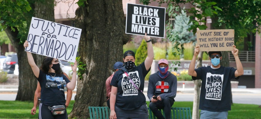 """Black Lives Matter supporters look on as Utah Business Revival hosts a """"Blue Rally"""" to support men and women of law enforcement and Utah's small businesses Saturday, June 20, 2020, in Salt Lake City."""