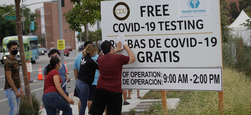 People fill out forms at a mobile coronavirus testing site at the Charles Drew University of Medicine and Science in Los Angeles on Wednesday.