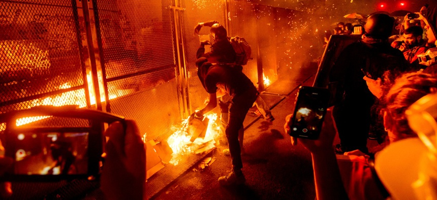 Protesters throw flaming debris over a fence at the Mark O. Hatfield United States Courthouse on July 22 in Portland, Ore. Following a larger Black Lives Matter Rally, several hundred demonstrators faced off against federal officers at the courthouse.