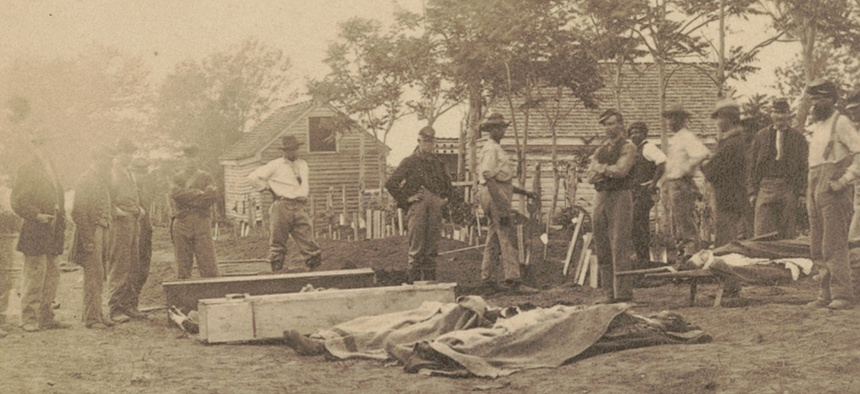Soldiers and African American workers standing near caskets and dead bodies covered with cloths during Grant's Overland Campaign.