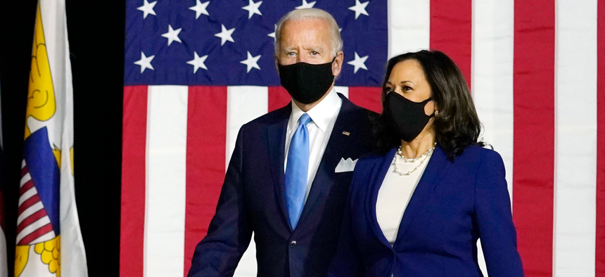 Democratic presidential candidate former Vice President Joe Biden and his running mate Sen. Kamala Harris, D-Calif., arrive to speak at a news conference at Alexis Dupont High School in Wilmington, Del., on Wednesday.