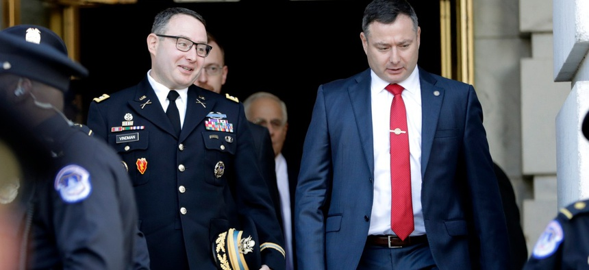 Then-National Security Council aide Lt. Col. Alexander Vindman, left, walks with his twin brother, Army Lt. Col. Yevgeny Vindman, after testifying before the House Intelligence Committee in November 2019.