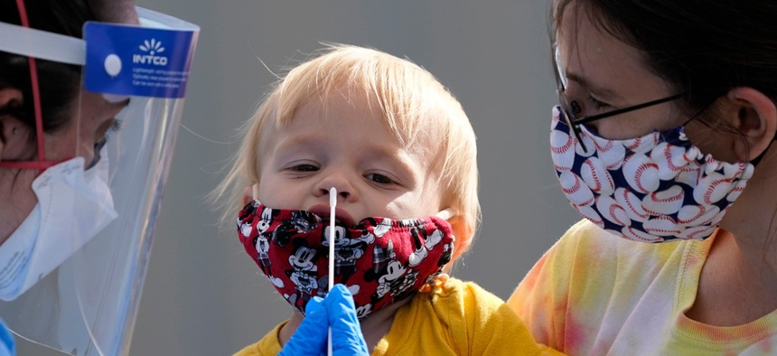 One-year-old Quentin Brown, is held by his mother, Heather Brown, as he eyes a swab while being tested for COVID-19 at a new walk-up testing site at Chief Sealth High School, Friday, Aug. 28, 2020, in Seattle.