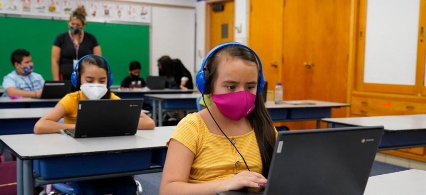 Reyna Najera, front, and her sister, Brenda, work on a laptops in a classroom in Newlon Elementary School early Tuesday, Aug. 25, 2020, which is one of 55 Discovery Link sites set up by Denver Public Schools.