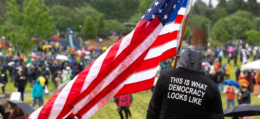 """Man wearing a """"This is what democracy looks like"""" shirt holds an American flag at a protest in Seattle in June."""