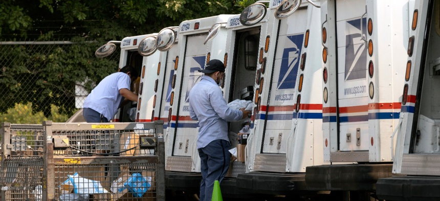 Postal workers load their mail delivery vehicles at the Panorama city post office on Thursday, Aug. 20, 2020 in the Panorama City section of Los Angeles.