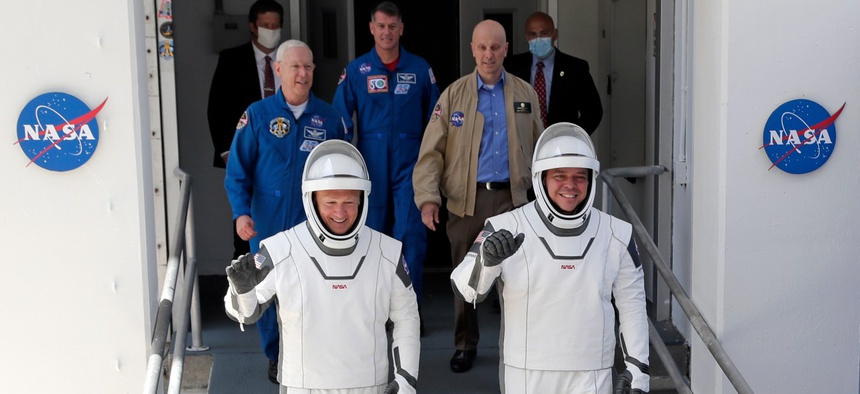 NASA astronauts Douglas Hurley, left, and Robert Behnken walk out of the Neil A. Armstrong Operations and Checkout Building on their way to Pad 39-A at the Kennedy Space Center in Cape Canaveral, Fla., on May 30.