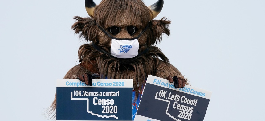 Rumble, the mascot of the Oklahoma City Thunder NBA basketball team, holds signs encouraging participation in the U.S. Census, at a drive-thru Census Mobile Questionnaire Assistance (MQA) event outside the state Capitol in Oklahoma City in September.