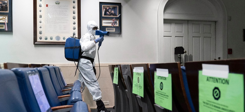 A member of the cleaning staff sprays the James Brady Briefing Room of the White House on Monday.