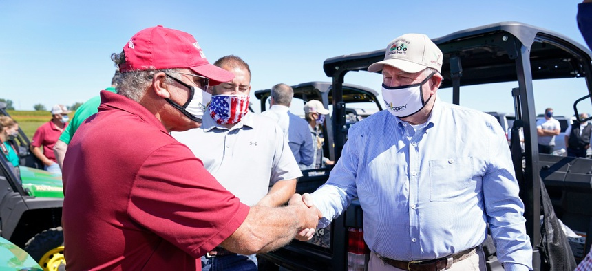 Agriculture Secretary Sonny Perdue, right, greets farmer Jim Greif, left, during a stop at the Heath Stolee farm, Thursday, Sept. 3, 2020, in Radcliffe, Iowa.