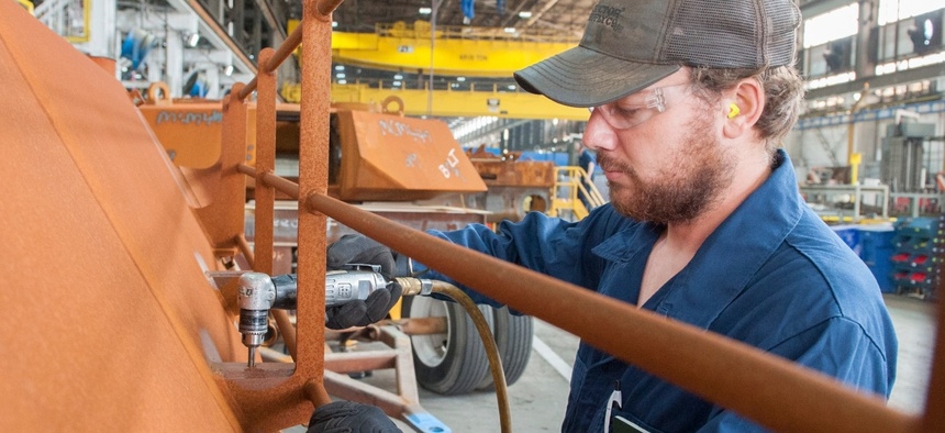 Randy Hollingsworth ensures the proper placement of holes on a M1 Abrams turret in Anniston Army Depot's Combat Vehicle Repair Facility.