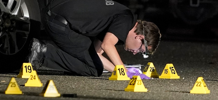 A Washington State Patrol Crime Lab worker looks at evidence markers in the early morning hours of Friday, Sept. 4, in Lacey, Wash. at the scene where Michael Reinoehl was killed.
