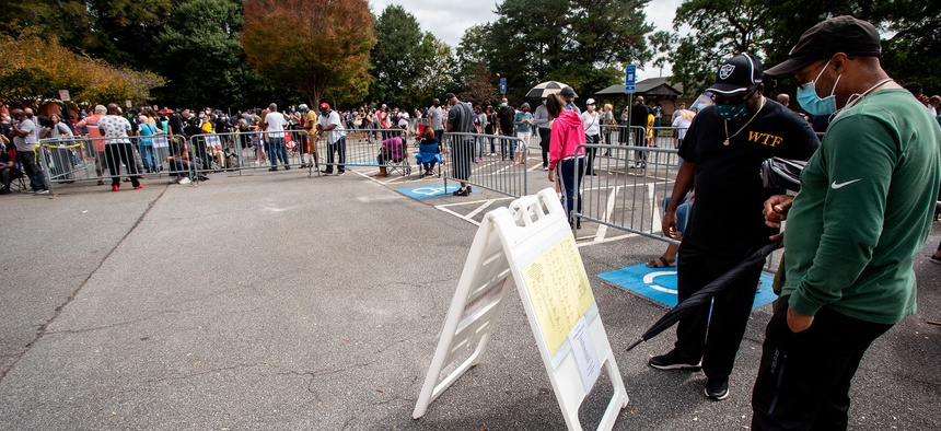Two men look at a sign containing voting information on Monday, Oct. 12, in Marietta, Georgia during early voting.