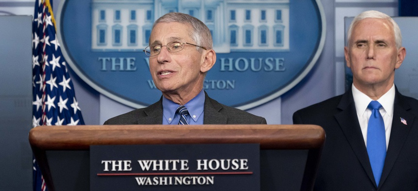 Fauci speaks at the White House in April as Mike Pence looks on.