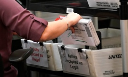 An election worker sorts vote-by-mail ballots at the Miami-Dade County Board of Elections on Oct. 26 in Doral, Fla.