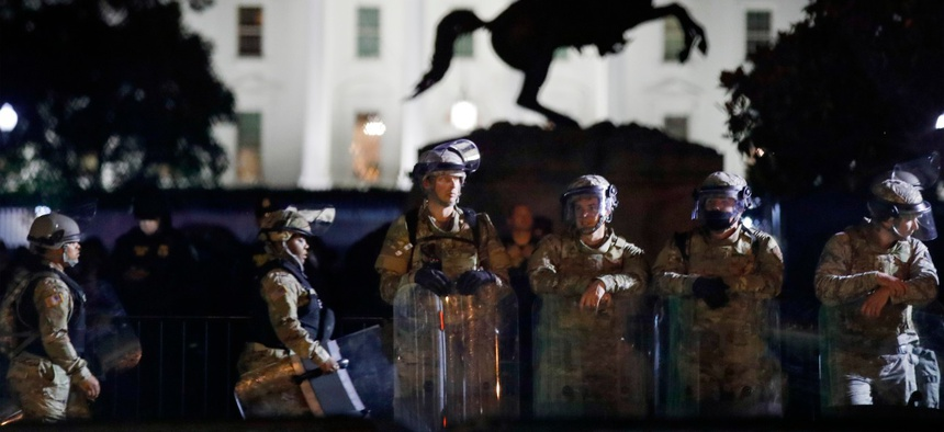 DC National Guard members stand in Lafayette Park as demonstrators gather June 2 to protest the death of George Floyd.