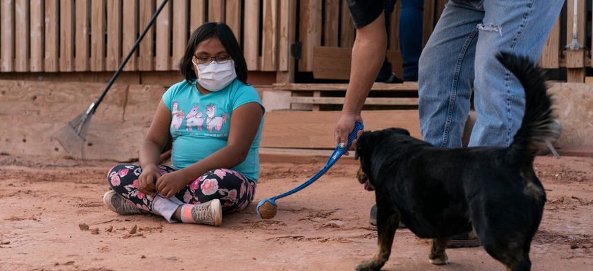 A girl watches her father play ball with their dog in April on a Navajo reservation in Tuba City, Arizona. Navajo Nation leaders say the Census Bureau did not spend enough time counting residents to avoid an undercount, a complaint echoed in Louisiana.