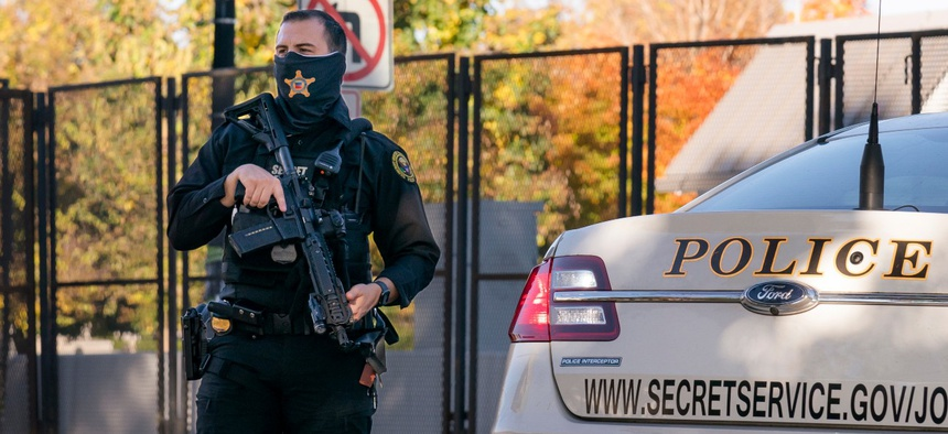 A Secret Service officer takes a position in the street as President Trump's motorcade arrives at the White House after golfing at his Trump National Golf Club in Sterling, Va., on Nov. 8.