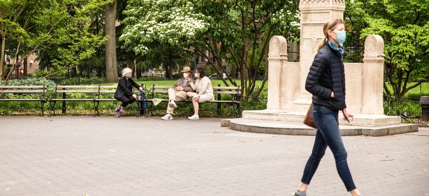 People are shown in New York's Washington Square Park in May.
