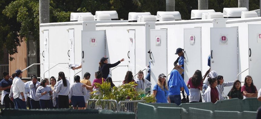 Migrant children stand outside portable restrooms at the Homestead Temporary Shelter for Unaccompanied Children, Monday, May 6, 2019, in Homestead, Fla.