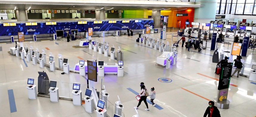 Travelers walk through the nearly empty JetBlue terminal at Logan Airport on Nov. 20 in Boston. With the coronavirus surging out of control, the nation's top public health agency pleaded with Americans not to travel for Thanksgiving.