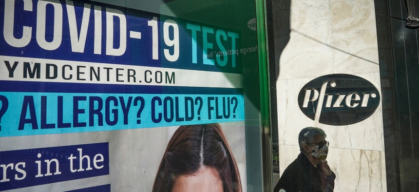 A bus stop ad for COVID-19 testing is shown outside Pfizer world headquarters in New York on Nov. 9. Pfizer has one of several promising coronavirus vaccine candidates.